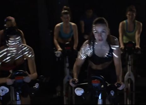 充满活力和自信的美女在健身房骑单车