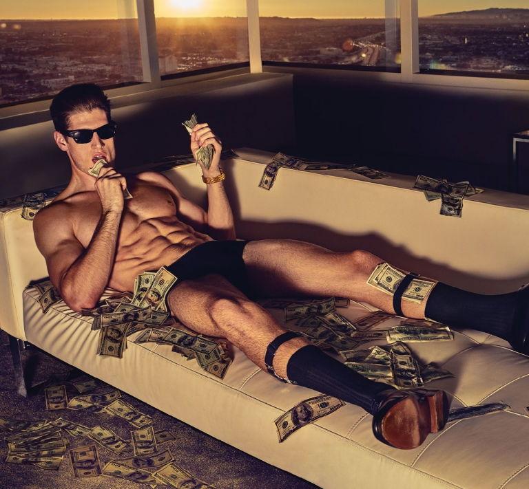 身材健美的猛男躺在钞票堆中